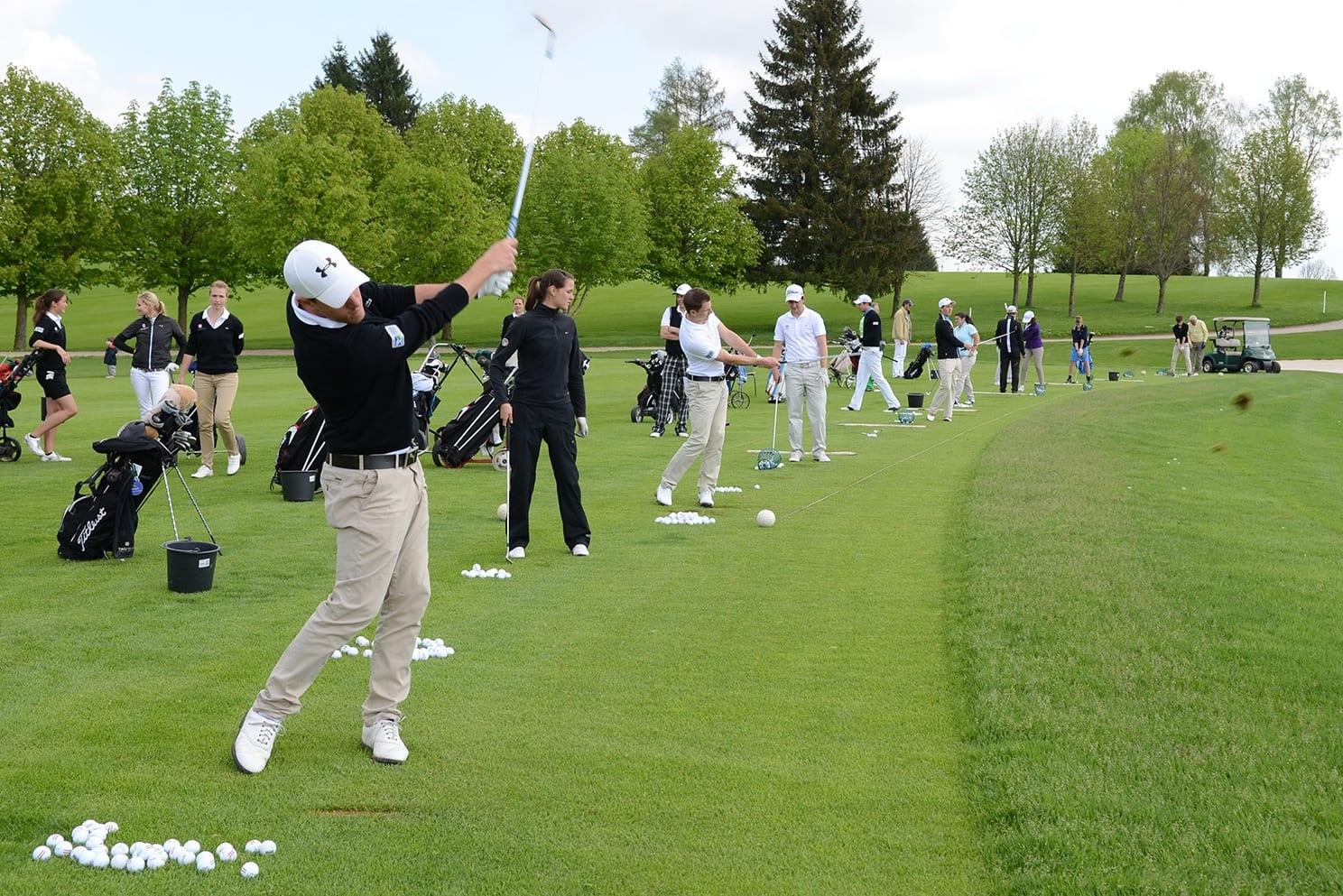 Hier sieht man Golfspieler beim Abschlag auf der Drivingrange.