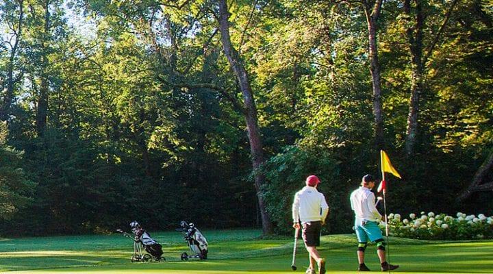 Zeigt zwei Golfer beim Golfspiel.